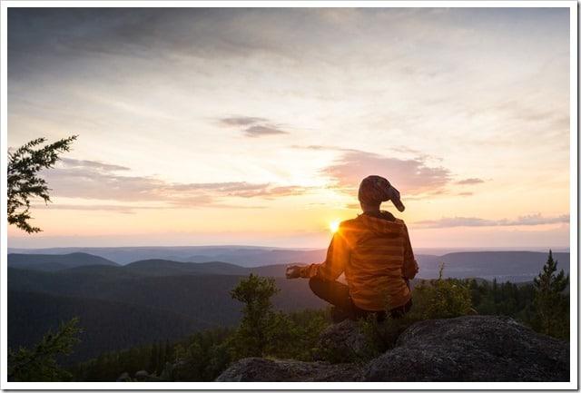 man meditating on a rock