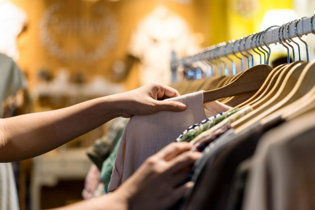 woman's hand looking through clothing rack representing ways to save money on clothes